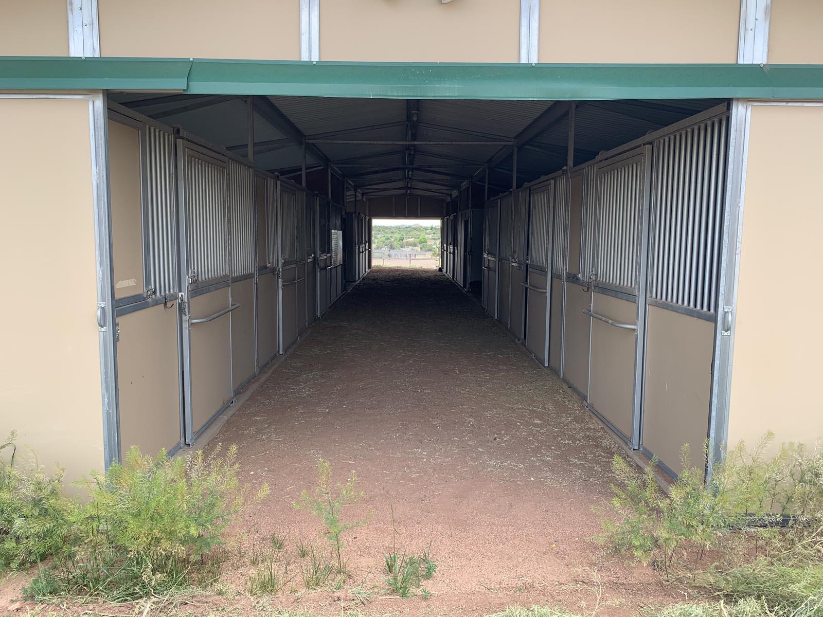 Barn aisle at Tiger Owl Ranch horse boarding facility in Santa Fe, New Mexico
